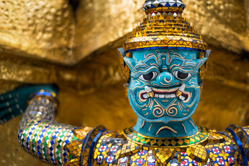 Stone guards decorated in brilliant mosaics hold up the Golden Temple at the Grand Palace, Bangkok Thailand